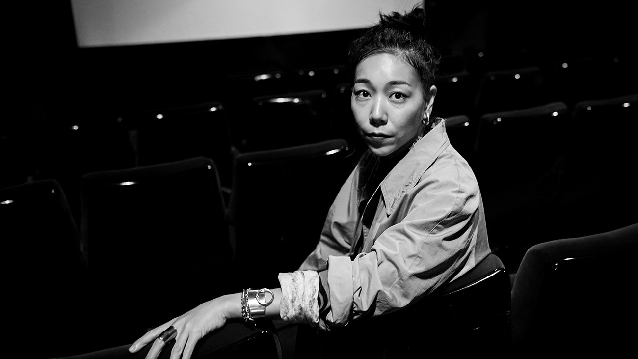 Black and white photo of director Momoko Ando sitting in a cinema.